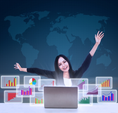 laptop stand: Happy businesswoman with arm raised looking at bar graphs