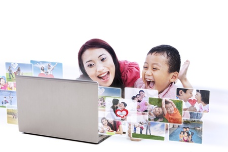 Happy young mother and her son laughing while looking at digital photos on white background photo
