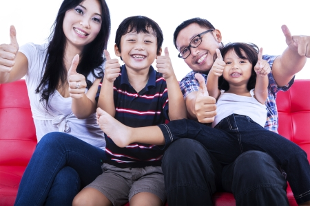 Portrait of asian family sitting on couch and showing thumbs up. Isolated on white background photo