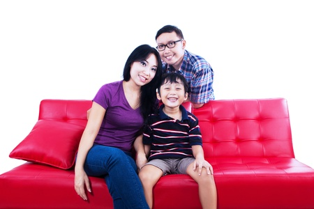 red sofa: Portrait of happy asian family sitting on couch. Isolated on white background
