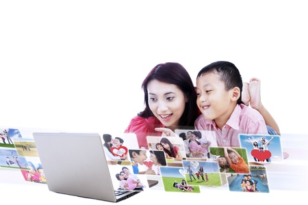 Young asian mother and her son looking at digital photos, isolated on white photo