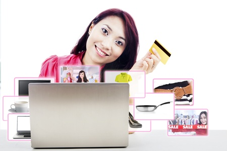 An attractive woman purchasing product online using her laptop computer and credit card, photo