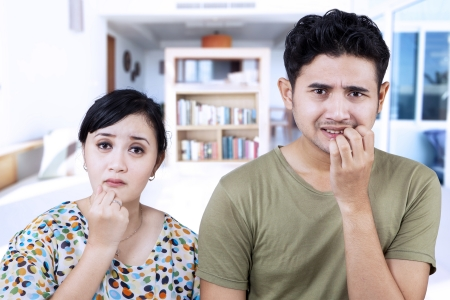 Afraid Asian couple biting nails at home Stock Photo - 21418899