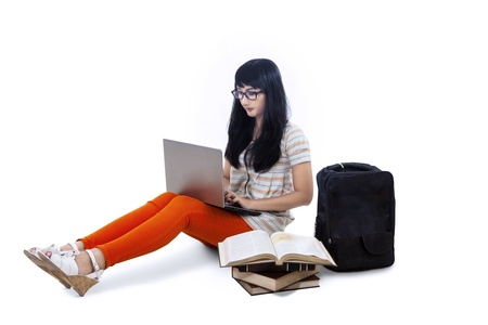 Asian female student typing on laptop on white background Stock Photo - 21418620