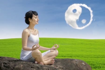 Girl practice yoga under ying yang cloud - outdoor Stock Photo - 21420140