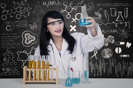 Beautiful young female scientist holding flasks on written blackboard photo