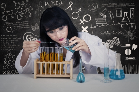 female scientist: Young female scientist is pouring liquid in classroom