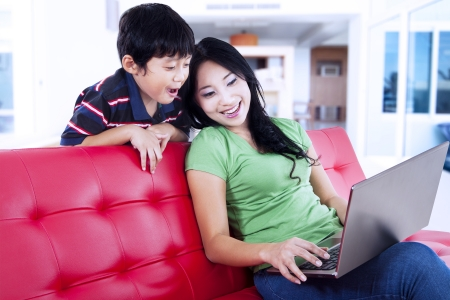 Mother and son looking at laptop in living room on red sofa photo