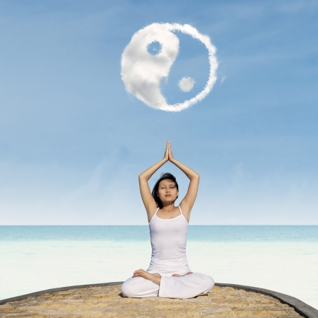 Young asian woman doing yoga exercise under Yin Yang cloud at beach Stock Photo - 21418950