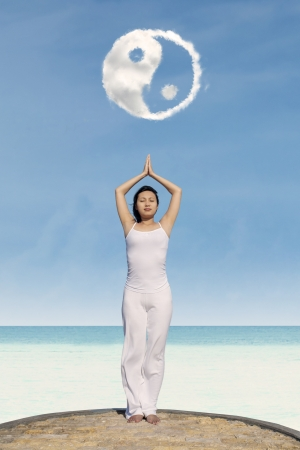 Young asian woman meditating under Yin Yang cloud photo