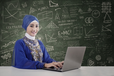 Portrait of beautiful teacher muslim in blue dress typing on laptop, shot in class photo
