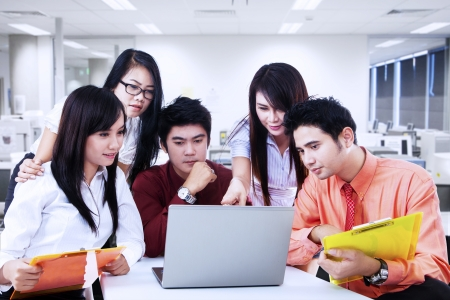 asian business team: Business team is having discussion by looking at laptop in the office
