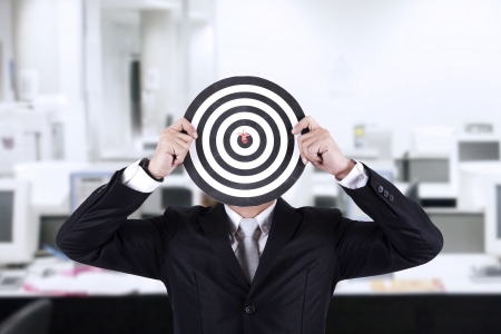 Businessman with bull's eye head dartboard in the office photo