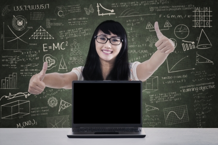 Portrait of happy college student giving thumbs up with copyspace on laptop. shot in class photo