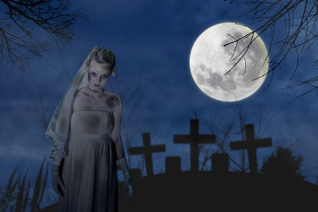 Halloween scene with creepy zombie bride on the dark night at graveyard Stock Photo