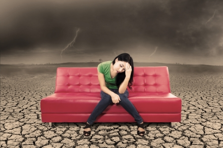 Picture of stress woman sitting on red sofa with cracking soil and bad weather photo