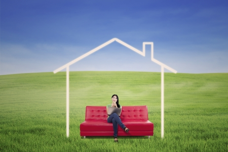 Beautiful woman in dream house sitting on red sofa with laptop photo