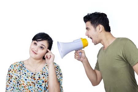 Angry boyfriend shouting at his girlfriend using speaker on white background photo
