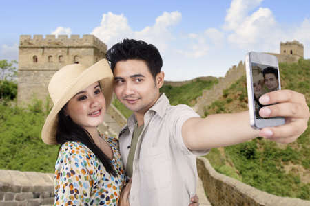 Asian couple take pictures at Great Wall of China with their smartphone photo