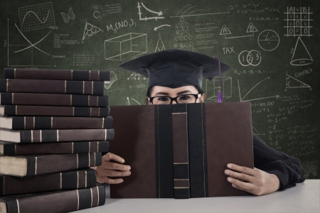 science class: Portrait of asian female graduate peeking from behind a book