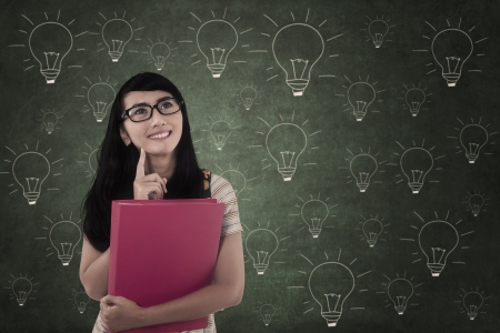 Asian student thinking of ideas in classroom on lightbulb drawing  photo