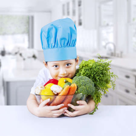 Boy chef wearing blue toque and vegetable at home photo