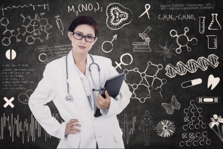 gp: Confident female doctor is holding e-tablet on written blackboard