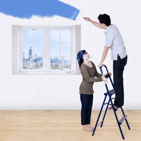 Couple painting new room in blue color  Stock Photo - 21778363