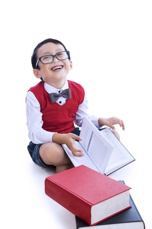 Cute boy is laughing while reading books on white background photo