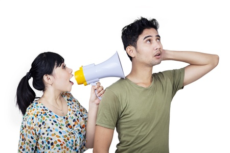 Girlfriend is shouting to her boyfriend using speaker on white background photo