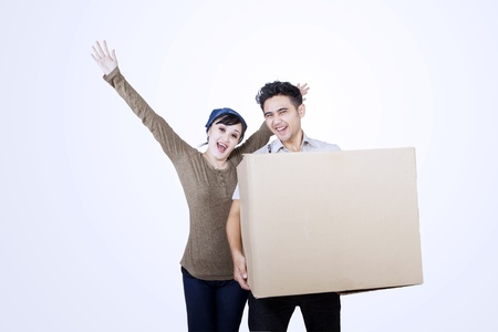 Happy couple carrying a blank box on white background photo
