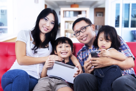 Happy family sitting on red sofa at home photo