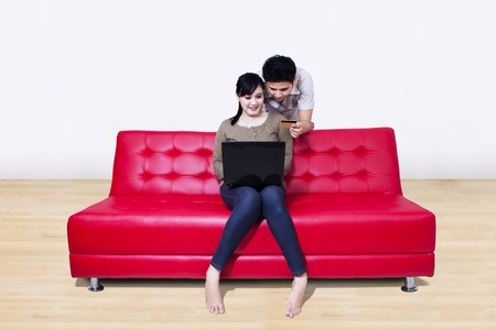 Beautiful couple pay online shopping using credit card on red sofa at home photo