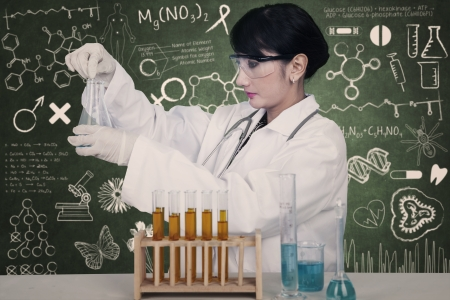 Beautiful female scientist working with yellow liquid on written chalkboard background photo