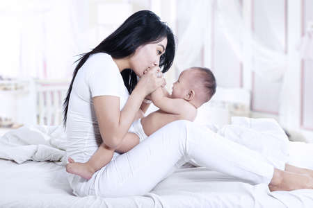 Attractive mother kissed her baby at home photo