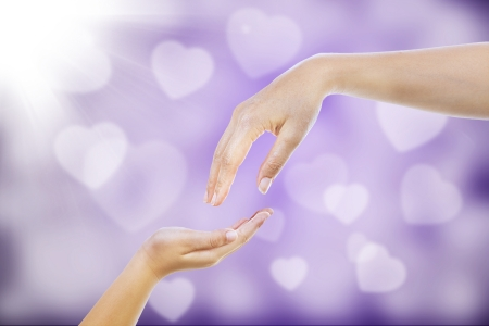 Giving hand gestures of a mother to a child on purple defocused lights photo