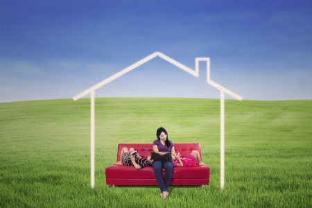 Mother and children enjoying on red sofa with dream house picture outdoor photo