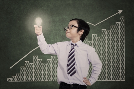 Little businessman holding lightbulb with bar chart background photo