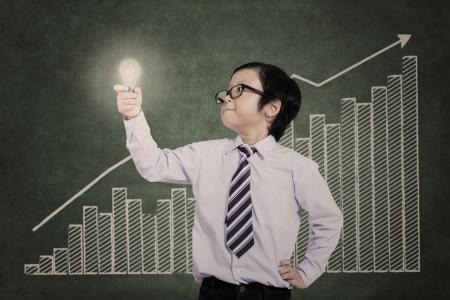 light classroom: Little businessman holding lightbulb with bar chart background Stock Photo