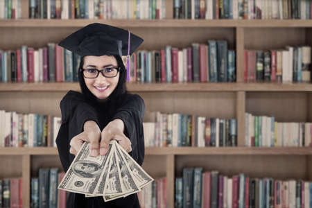 Young female graduate holding money at library  photo