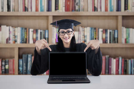 Graduate student pointing at empty black screen laptop  shot in library photo