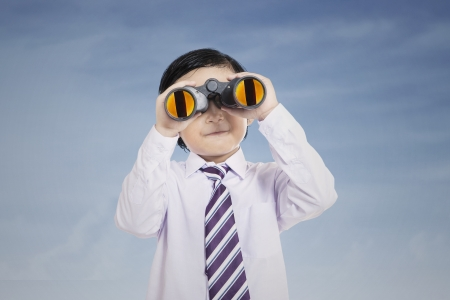 Business kid looking through binoculars under blue sky photo