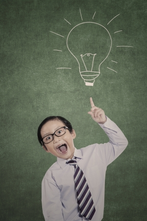 light classroom: Bright business kid pointing his finger on hand drawn lightbulb