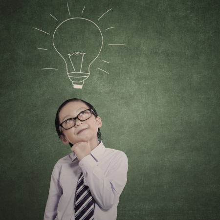 Smart business kid thinking on hand drawn bulb background photo