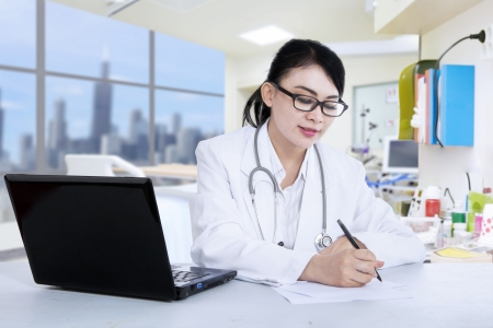 Attractive female doctor is writing prescription at the clinic photo