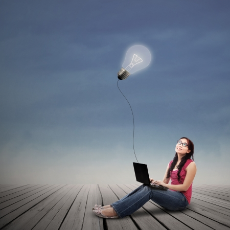 woman laptop: Beautiful female student looking at lit bulb with laptop outdoor Stock Photo