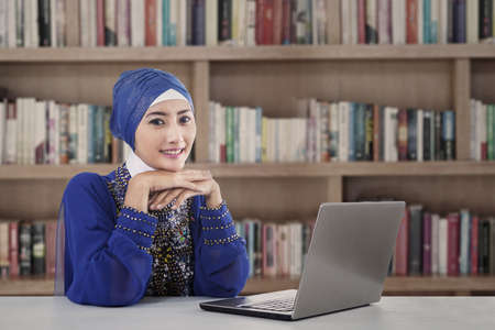 Beautiful muslim girl study with laptop at library photo