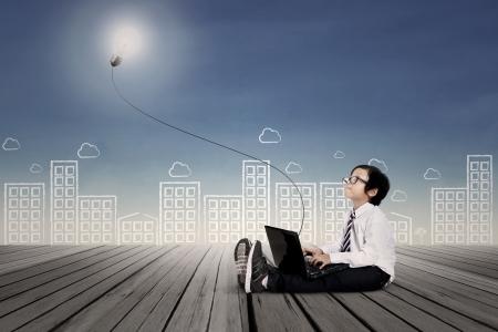 Business boy Eingabe auf Laptop Unterstrichen es Glühbirne Außen Standard-Bild - 21985554