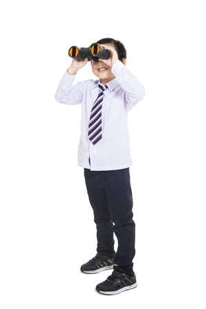 Little businessman holding binoculars on white background, vertical shot photo