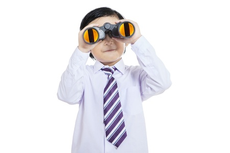 Close-up of business kid holding binculars on white photo